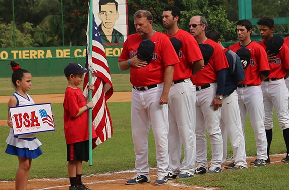 Richmond head coach Tracy Woodson, assistant coach Matt Tyner, pitching coach Josh Davis, and Spiders players stand in respect for the United States and the Cuban national anthems before the game against Pinar del Rio. - UNIVERSITY OF RICHMOND ATHLETICS