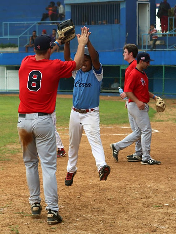 Michael Morman high-fives the batboy midgame against La Habana. - UNIVERSITY OF RICHMOND ATHLETICS