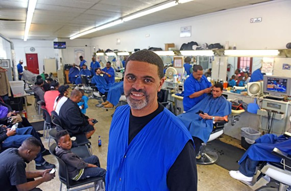 Barbershop owner Melvin McCormick has a steady flow of customers on a recent warm Saturday. He says he's optimistic that more development will help business skyrocket. - SCOTT ELLMQUIST