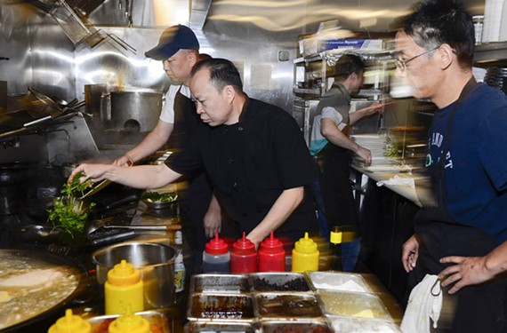 In his busy Short Pump kitchen, Chang demonstrates for his staff exactly how his dishes should be prepared. With eight locations and two more about to open, Chang must train all of the chefs to duplicate the way that he cooks. - ASH DANIEL