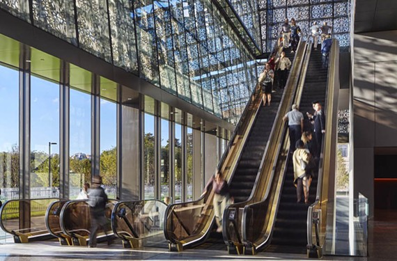 Museum visitors travel by escalators to reach the underground and upper exhibition areas. - ALAN KARCHMER/NNAMHC