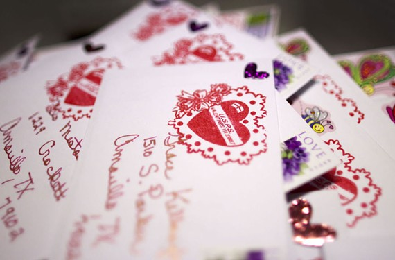 Postmaster Kathryn Fajna marks each Valentine she receives with a red heart cachet for Valentines Day. - BILL TIERNAN