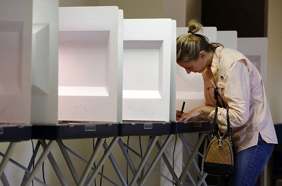 Julie Peollnitz selects her candidates at the voting booth at Emanuel A.M.E. Church in Portsmouth. - THE' N. PHAM