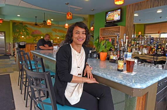 "Carena Ives serves a variety of local beer at Carena's Jamaican Grill: ""Putting 'craft' in front of it makes it this other thing."" - SCOTT ELMQUIST"