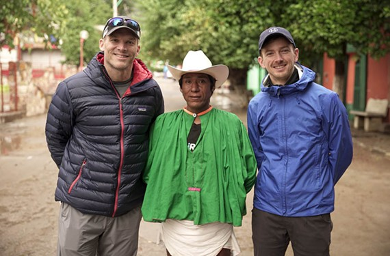 "Health Warrior's co-founder, Nick Morris, and its chief financial officer, Austin Harris, meet with Arnulfo Qimare, the Tarahumara runner made famous in ""Born to Run,"" on a visit last year to the Barrancas. Qimare competed in the 2016 Boston Marathon wearing handmade huaraches and traditional garb. - HEALTH WARRIOR"