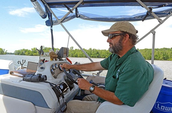 Mike Ostrander captains his pontoon boat on the south James, where he offers eagle tours that show off the natural beauty and history of the area, near where Dominion's Chesterfield Power Station has its coal ash wastewater ponds. - SCOTT ELMQUIST