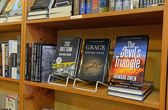 """Howard Owen's Willie Black series lines a shelf at Chop Suey Books in Carytown. The latest, """"The Devil's Triangle,"""" opens with a small plane crashing into the titular neighborhood — an informal name for the commercial area surrounding the Sheppard Street 7-Eleven in the Museum District. - SCOTT ELMQUIST"""