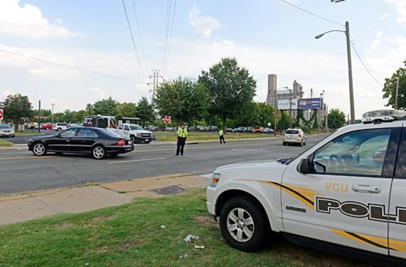 At rush hour, police direct traffic leaving the Virginia Commonwealth University lot on Mayo's Island. - SCOTT ELMQUIST