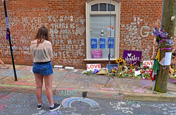 The street and sidewalk where Charlottesville resident Heather Heyer was killed during last year's rally overflow with flowers, signs and chalk-written messages of love and peace. - SCOTT ELMQUIST