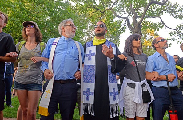 Local clergy join arms in protest near Brooks Hallon Saturday - evening. - SCOTT ELMQUIST