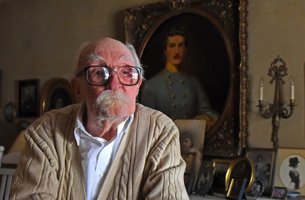 """Robert """"Bobby"""" Willis Jr. at home among his many photographs paintings and books. The framed portrait at right is of Joseph Melville Willis, a great-great-uncle who was killed in 1862 at the Battle of Seven Pines near Richmond during the Civil War. It was painted by Willis' mother, Edith Duesberry Willis. - SCOTT ELMQUIST"""