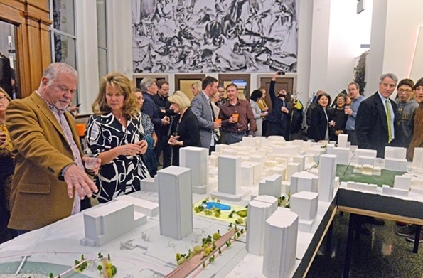 Architects, planners and civic leaders examine the 25-foot-long scale model of BridgePark in the Mobelux Building lobby Nov. 8. Plans were displayed in conjunction with the annual meeting of the Virginia Society of the American Institute of Architects. - SCOTT ELMQUIST