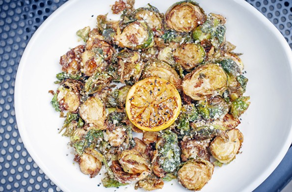 The Brussels sprouts are fried to a crisp and topped with Parmesan cheese and lemon. - ASH DANIEL