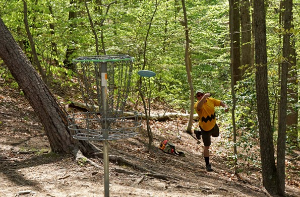 Scott Holter throws a disc toward a basket in a game of disc golf during the Virginia State Tournament held in Fredericksburg in April. - LARRY SCHINDELL