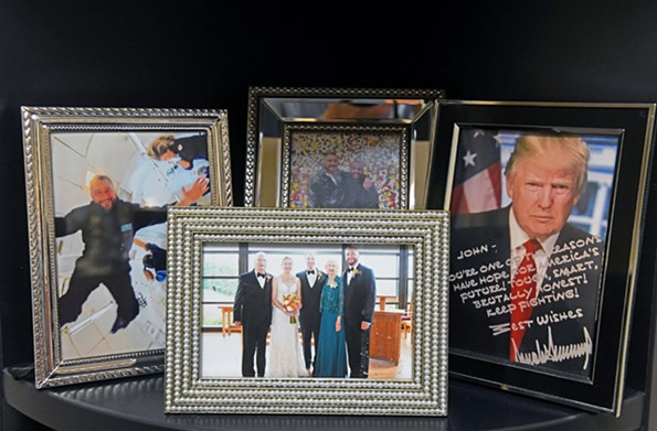 Reid's office at WRVA is filled with memorabilia from travels to 85 countries and political campaign trinkets. Framed photos include a zero-gravity NASA experience Reid took, a family picture at his sister's wedding, he and his partner, Alonzo, and a signed photo from President Trump. - SCOTT ELMQUIST