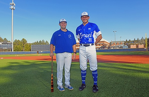 Nate Mulberg, assistant baseball coach of the Israeli team and at the University of Richmond, poses with Jonathan de Marte in Olympic uniform at Pitt Field. - SCOTT ELMQUIST