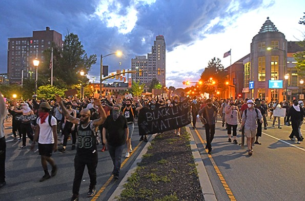 Protesters march down Broad Street on Sunday evening near the Greater Richmond Convention Center. - SCOTT ELMQUIST