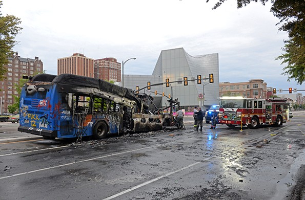 Richmond firefighters examine a burned out GRTC bus at Belvidere and Broad streets early Saturday. The bus was set on fire late Friday, May 29. - SCOTT ELMQUIST