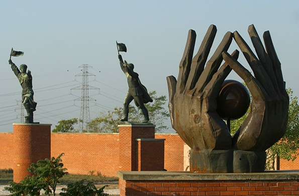 """The """"Workers' Movement Memorial"""" (foreground, designed by Kiss Istvan in 1975) and the """"Captain Miklos Steinmetz Statue""""  (sculpted by Mikus Sandor in 1958 to honor a Hungarian-born Soviet Red Army officer) are among 42 heroic sculptures that were removed from prominent Budapest sites after the fall of communism in 1989 and reinstalled in Memento Park on the city's outskirts."""