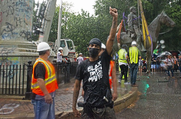 A young man raises his fist in the pouring rain just after the removal of the Stonewall Jackson statue July 1. - SCOTT ELMQUIST
