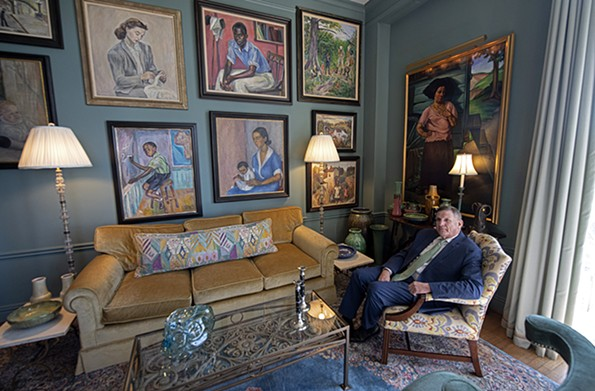 """Keith Kissee, a collector of American andEuropean art from the firsthalf of the 20th century, sits beneath works by Virginia-born artist Harriet Fitzgerald (1904-1984) displayed on the east wall of his living room. Danville native Fitzgerald, who studied with John Sloan at the Art Student's League in New York, oftenpainted the everyday people and scenes of her hometown. A work by California WPA artist Otis Oldfield, """"La Bohemian,"""" hangs on the adjacent wall. - SCOTT ELMQUIST"""