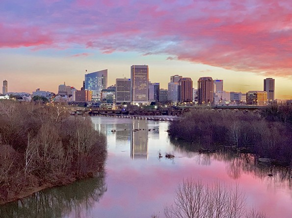 The city stretches beneath pink clouds.