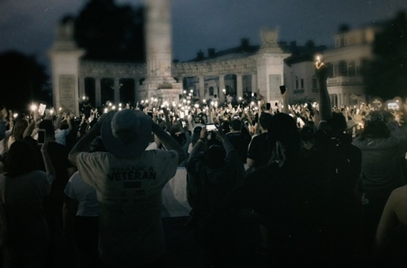 """A film still from """"How the Monuments Came Down,"""" of a vigil being held at the Jefferson Davis Monument."""