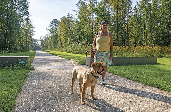 Vivian Lee Messner, a long-time Colonial Beach resident, walks Barney along the Time Trail at the Monroe birthplace. - SCOTT ELMQUIST