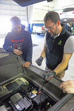 Car repair technician Anil George is taught how to place a wireless module in a Chevrolet Volt by Jake Rath, vice president of operations at Evatran. - SCOTT ELMQUIST