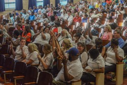 The crowd reacts to a commenter at George Mason Elementary School's auditorium. - SCOTT ELMQUIST