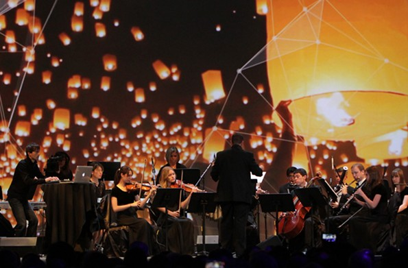 Bates, at far left, is known for incorporating electronic sounds and usually stands in the thick of the orchestral action behind a laptop or drum pad.