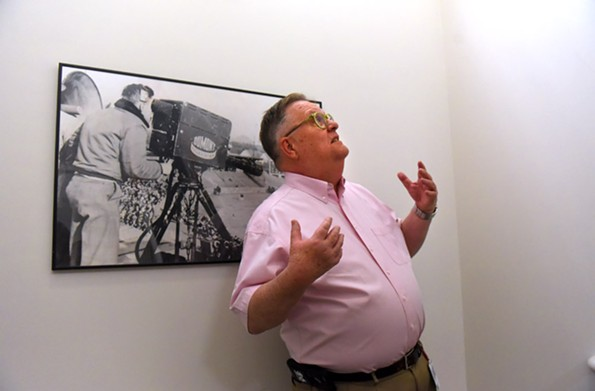 Don Talley gestures in front of a picture of WTVR's first televised John Marshall High School baseball game, 1950. - SCOTT ELMQUIST