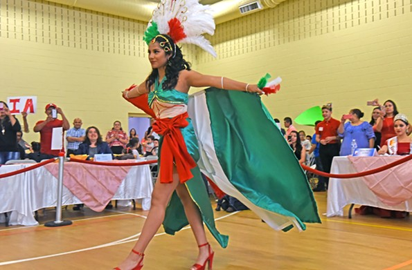 Thalia Gomez struts in her handmade outfit representing the colors of the Mexican flag during the May 6 talent show. - SCOTT ELMQUIST