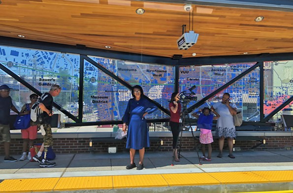 At Willow Lawn on West Broad Street, riders and a WTVR-6 camera operator await an eastbound bus on June 24, the first day of the Pulse system. - SCOTT ELMQUIST