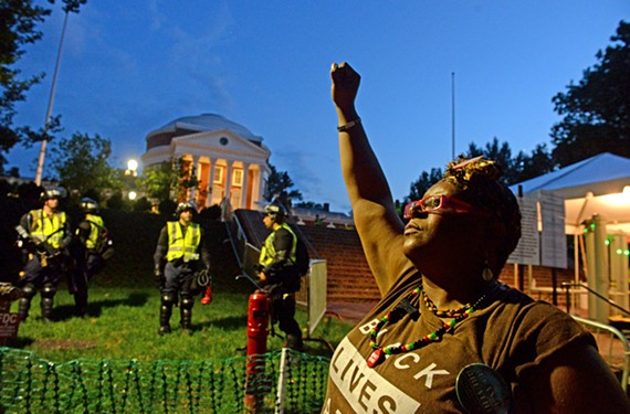 As the Virginia State Police guard the Rotunda at U.Va., Rosia Parker raises a fist in the last light of day on Saturday evening.