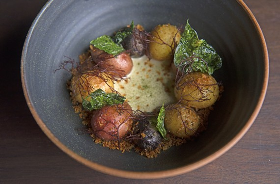 Roasted potatoes with koji cream, potato greens, seaweed and potato crumble.