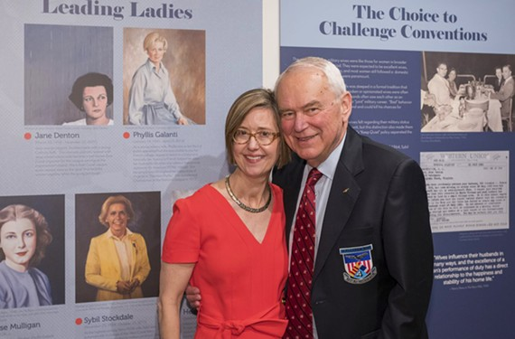 Heath H. Lee and Paul Galanti stand before portraits of some of the women featured in Lee's book, including Phyllis Galanti in the top row to the left of Lee.