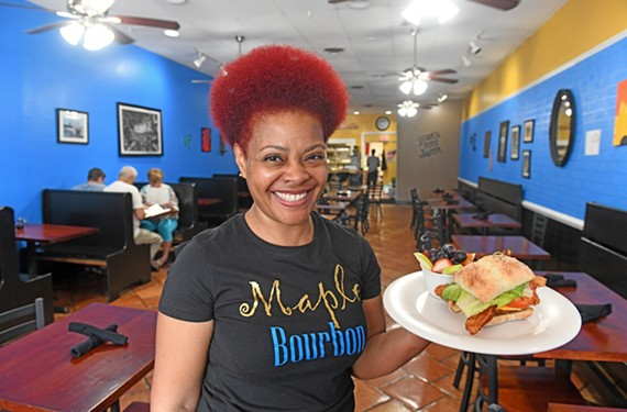 Maple Bourbon owner Jaynell Pittman-Shaw holds the Can We Talk, a sandwich featuring fried chicken breast, bacon, lettuce, tomato and cheese.