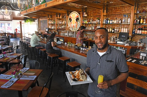 Assistant manager Kevin Alexander at Brunch,the newest concept by the team behind the Scott's Addition restaurants Lunch and Supper, holds chicken and waffles with a mimosa.