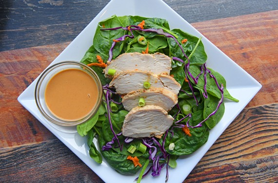 Roasted chicken tops a bed of mixed greens, purple cabbage, spring onions and carrots with a side of spicy Asian peanut dressing.