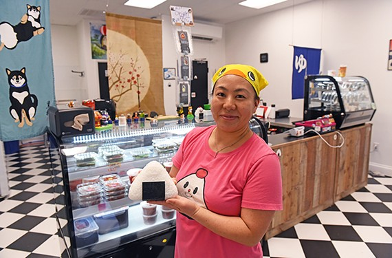 Owner Wakoko Reno holds an onigiri — a stuffed triangle of sticky rice wrapped in dried seaweed.