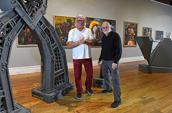 "Longtime local artists Darryl Starr and Wolfgang Jasper stand with their work inside the Black Iris Gallery at 321 W. Broad St. The exhibition ""Famous Duo: 1989-2019"" runs through Nov. 29."