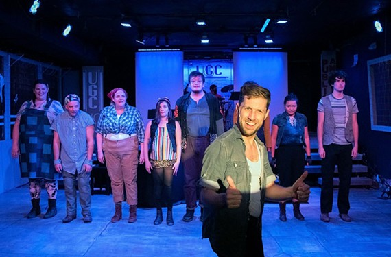 "Actor Matt Shofner stands in front of the cast of TheatreLab's ""Urinetown,"" which serves up ""hard-hitting satire and genuinely good show tunes."""