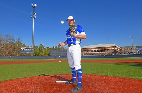 University of Richmond alumnus Jonathan de Marte, who played baseball for the Spiders, will compete for Israel at the Tokyo Olympics this summer. He's standing on the school's Pitt Field, with the Robins Center in the background.