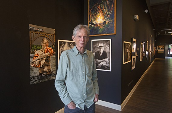 "Photographer John Henley stands near the front of his current exhibit, ""Artists,"" at Glavé Kocen Gallery. It runs through July 18 and is the Main Street gallery's final show after 17 years of highlighting local artists."
