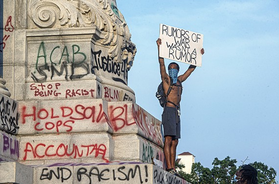 Cliff Chambliss holds the sign he created while standing on the pedestal of the Robert E. Lee statue on June 6.