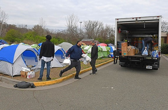 Volunteers from Blessing Warriors load trucks with supplies on March 18, the day Camp Cathy was dismantled.