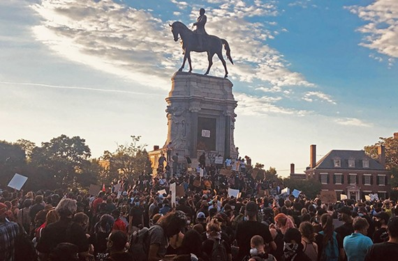 Protesters gathered around Robert E. Lee statue at sunset.