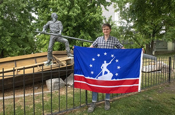 """VCU adjunct professor Barry O'Keefe holds up a Richmond city flag redesigned in 1993 to celebrate """"anonymous laborers of all races who built the city,"""" which he recently used as a model for his class."""
