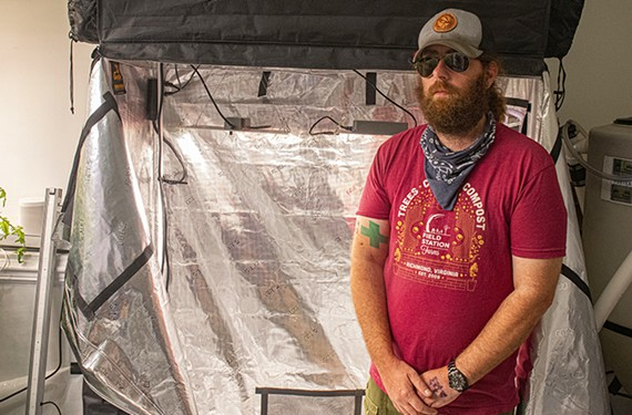 Chris Haynie, co-founder of Happy Trees Agricultural Supply in Scott's Addition, advises newbies to start by growing cannabis indoors because of the many outdoor challenges in Virginia. He's standing in front of a starter enclosure tent sold at his store.
